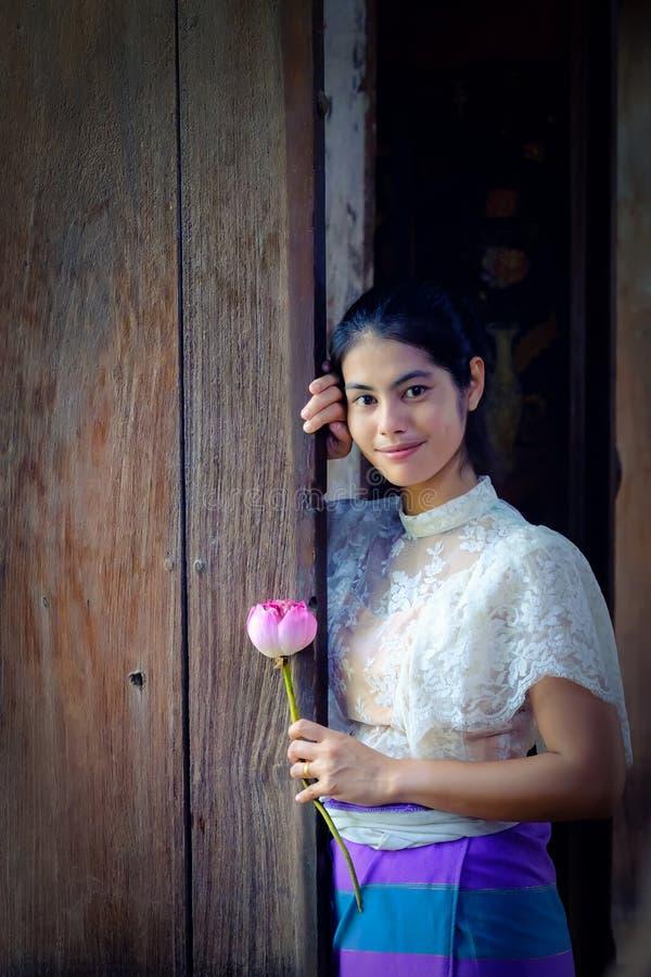 Fille traditionnelle thaïlandaise de robe tenant l'ol proche disponible de fleur de lotus images stock
