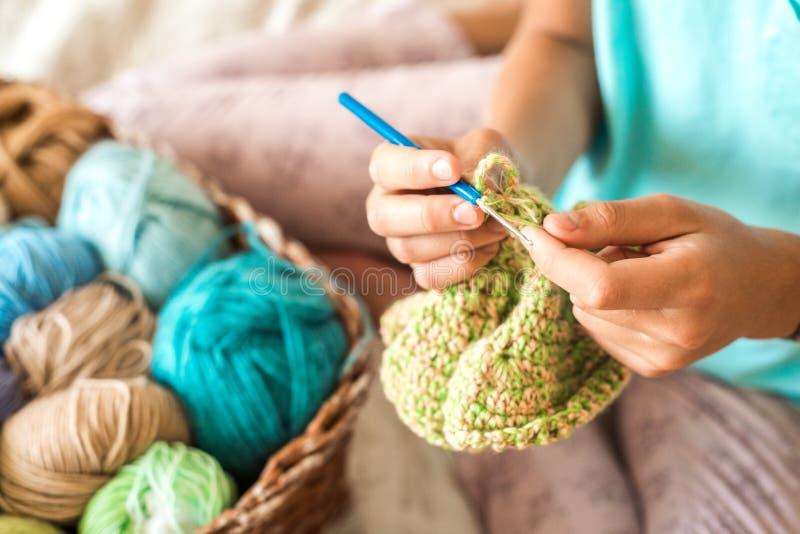 Fille tricotant à la maison Boules multicolores de fil de tricotage dans le panier et une écharpe blanche tricotée image stock