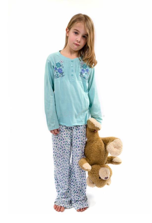 Fille triste dans des pyjamas avec teddybear image libre de droits