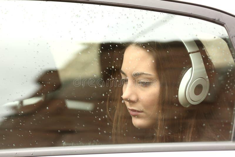 Fille triste d'adolescent dans une voiture avec des écouteurs image libre de droits