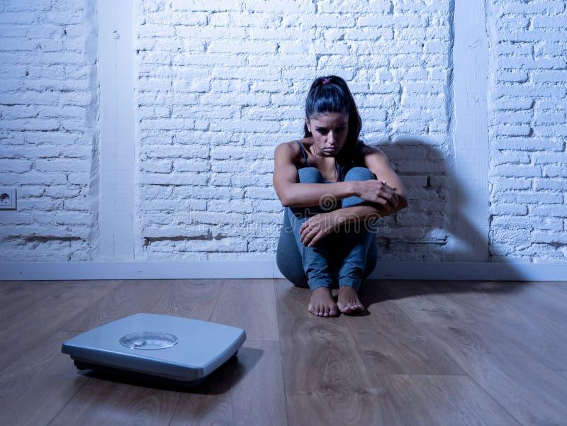 Fille triste de femme ou d'adolescent effrayée du poids regardant l'échelle dans le trouble de la nutrition photo libre de droits