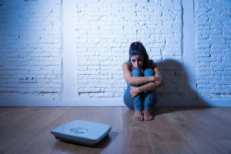 Fille triste de femme ou d'adolescent effrayée du poids regardant l'échelle dans le trouble de la nutrition images libres de droits