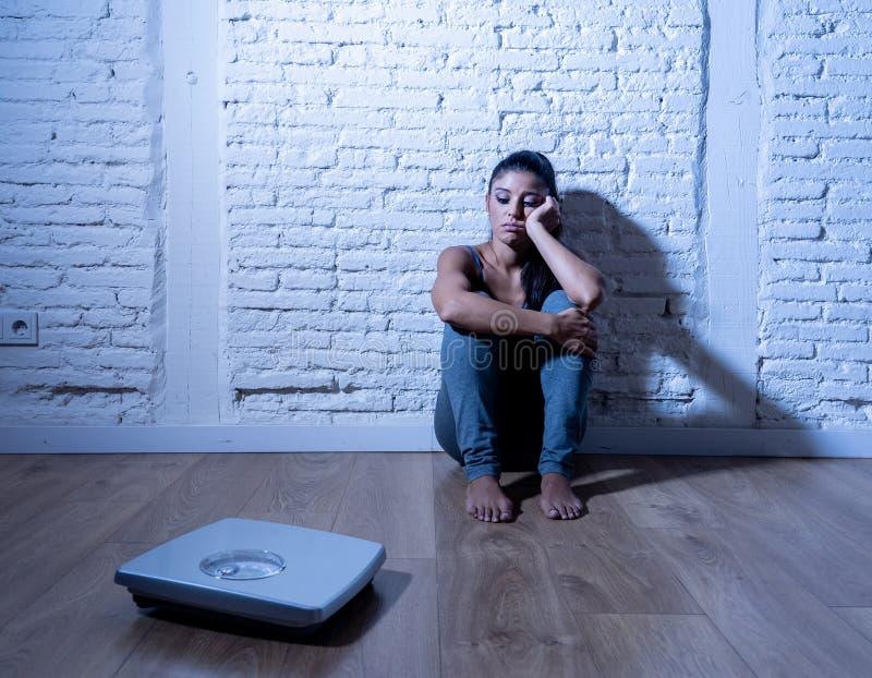 Fille triste de femme ou d'adolescent effrayée du poids regardant l'échelle dans le trouble nutritif image libre de droits