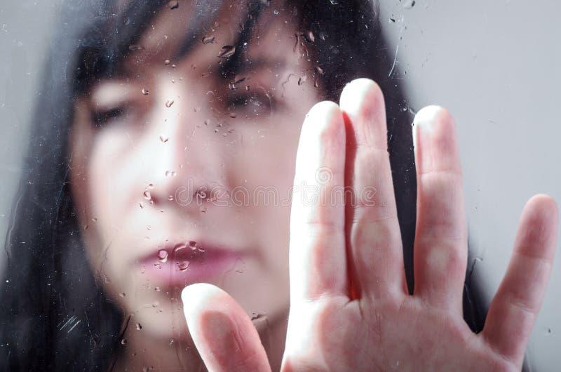 Fille triste derrière le verre humide image stock