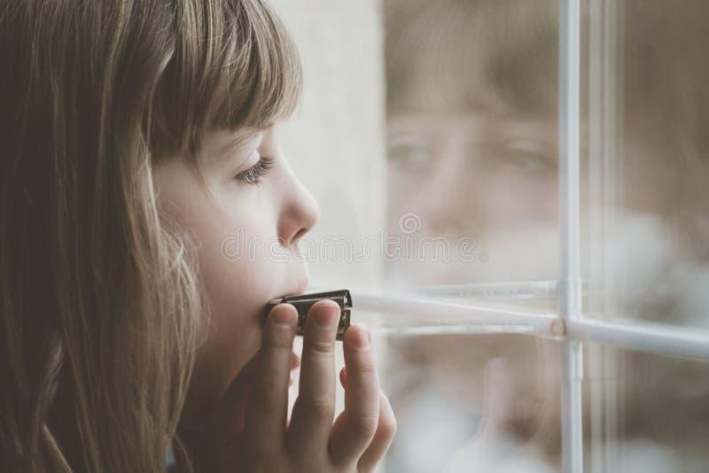 Fille triste jouant l'harmonica photographie stock