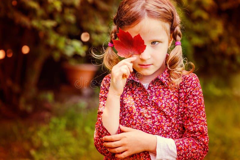 Fille triste mignonne d'enfant se cachant derrière la feuille rouge d'automne dans le jardin photos libres de droits