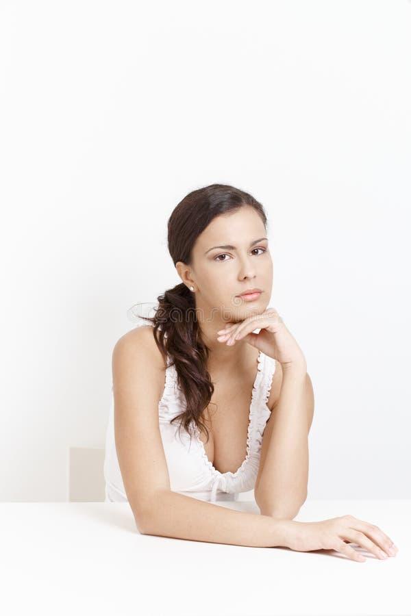 Fille triste s'asseyant au-dessus du fond blanc photographie stock libre de droits
