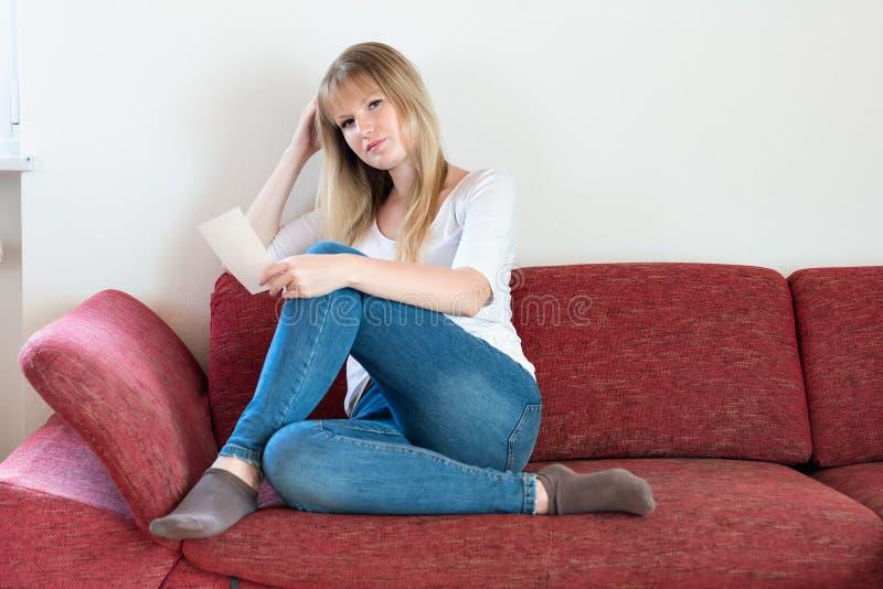 Fille triste s'asseyant sur le sofa photographie stock libre de droits
