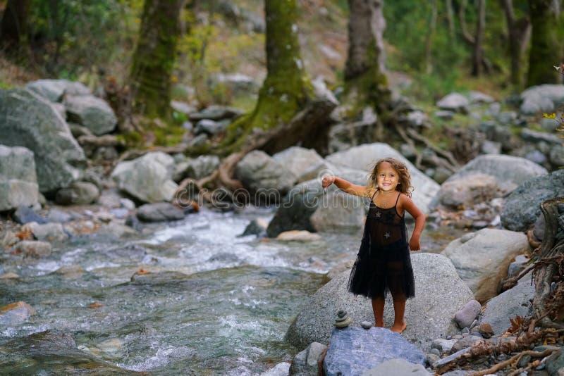 Fille trois an jouant avec une vieille poupée près d'une rivière dans la belle nature de la montagne de Dirfi dans Eubeoa photographie stock