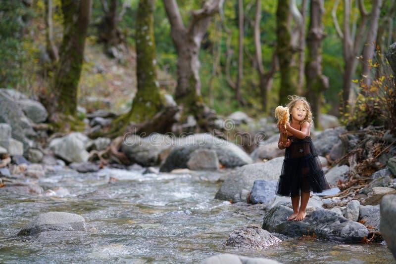 fille trois an jouant avec une vieille poupée près d'une rivière dans la belle nature de la montagne de Dirfi dans Eubeoa photo stock