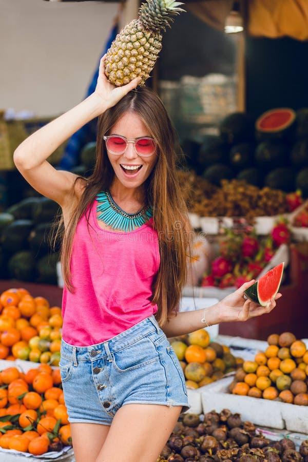 Fille tropicale d'été dans des lunettes de soleil roses sur le marché sur le fond de fruits Elle tient l'ananas sur la tête et la images stock