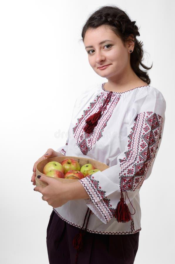 Fille ukrainienne retenant un bluteur avec des pommes photographie stock