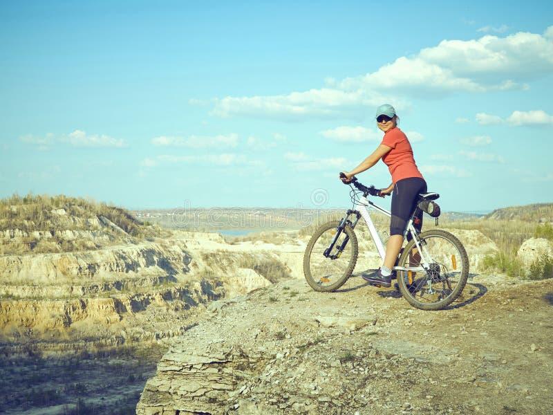 Fille un vélo en montagnes image stock