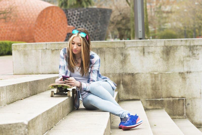 Fille urbaine de beau hippie avec la planche à roulettes et le téléphone portable photo libre de droits