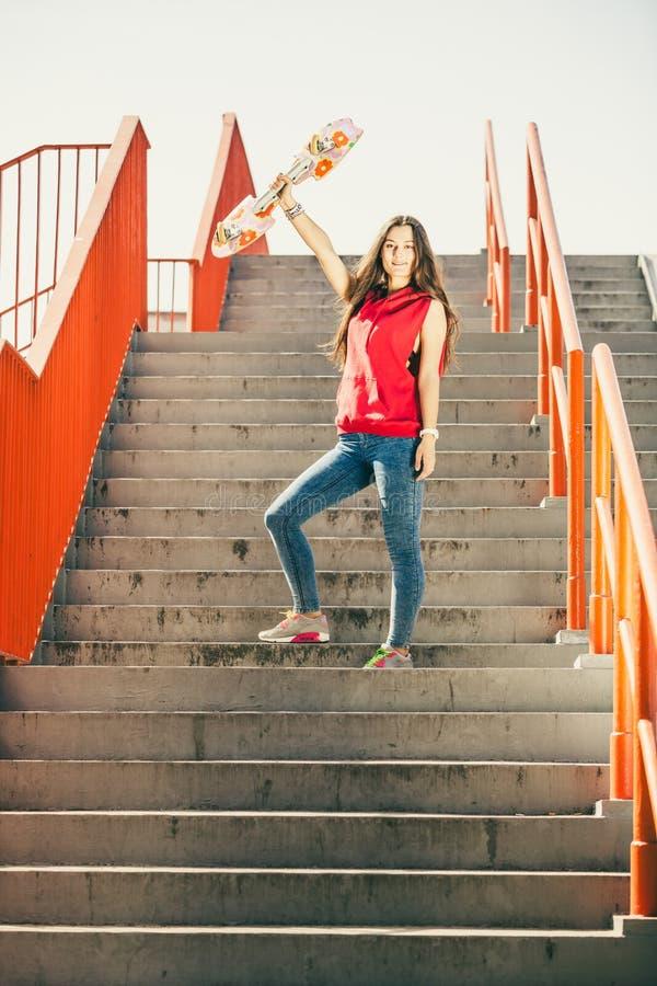 Fille urbaine de patin avec la planche à roulettes photos stock