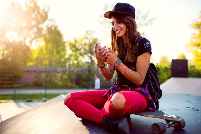 Fille urbaine mignonne dans le skatepark avec la planche à roulettes utilisant le téléphone intelligent photographie stock
