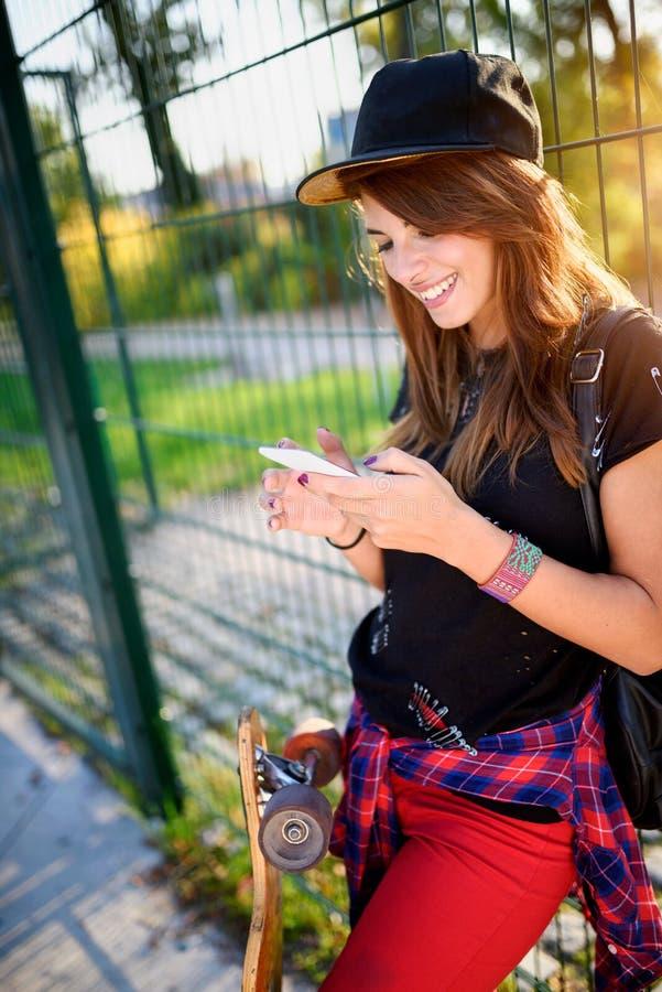 Fille urbaine mignonne en parc de patin avec la planche à roulettes utilisant le téléphone intelligent images stock