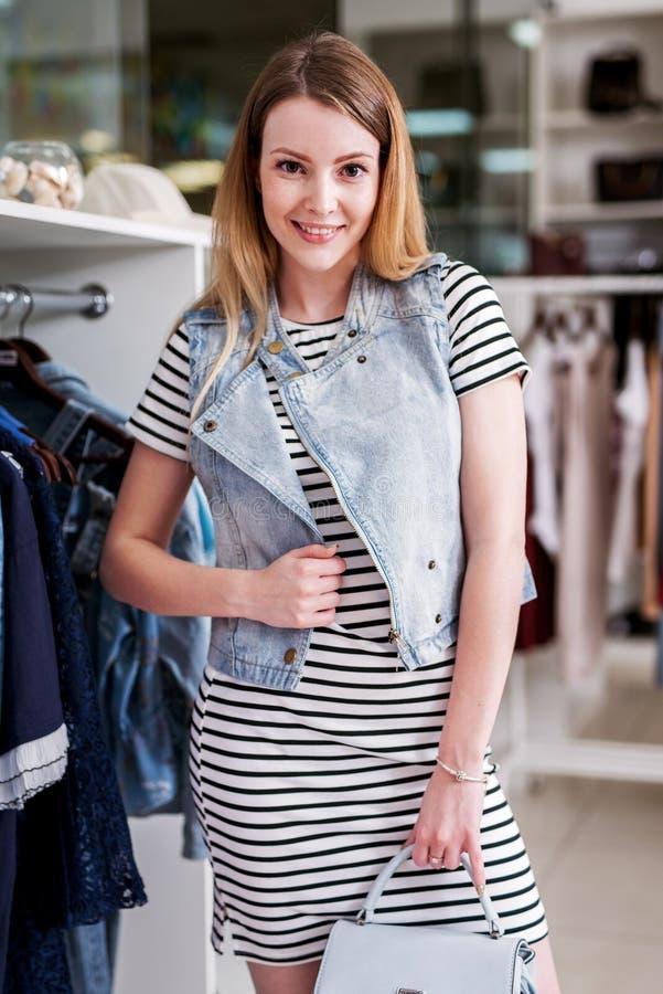Fille utilisant la robe, le gilet de denim et le sac à main barrés de la collection d'été dans une boutique de mode photo libre de droits