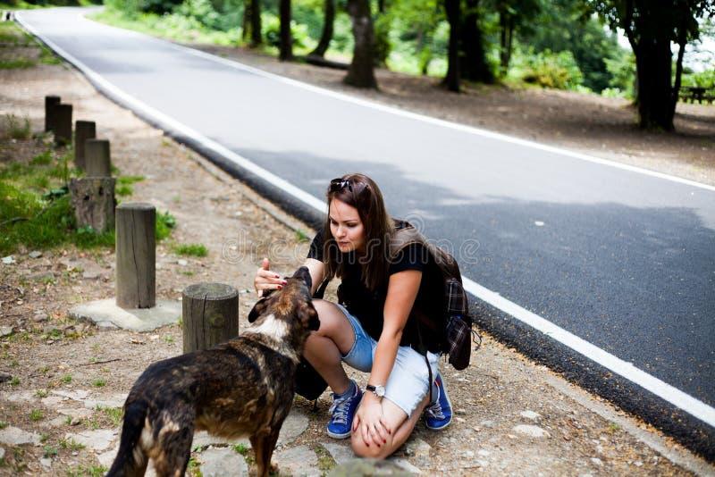Fille voyageant avec un chien sans abri image libre de droits