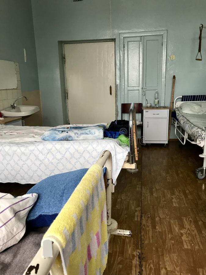Filled beds of patients and their personal belongings left on the beds and nightstands. The old hospital from the inside. Filled beds of patients and their stock photo
