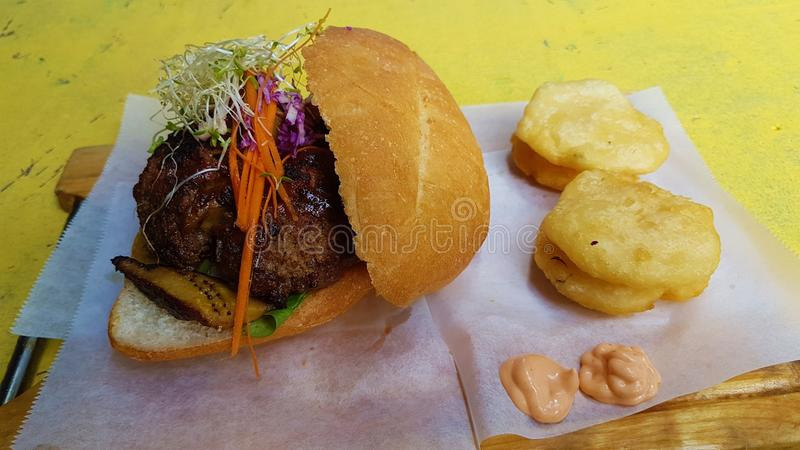 Filled burger and fried yucca stock image