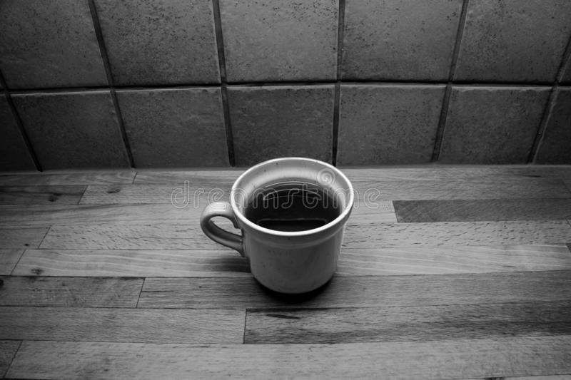 A filled cup of tea stands on a wooden countertop in front of a tiled wall. A cup of tea stands on a wooden countertop in front of tiled kitchen wall royalty free stock images