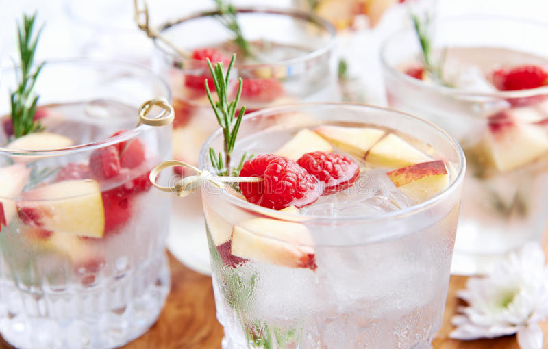 Filled with fruity flavour -Cocktails. Close up of clear cocktails/soda water being served on a wooden tray decorated with flowers, raspberries, sliced nectarine stock photography