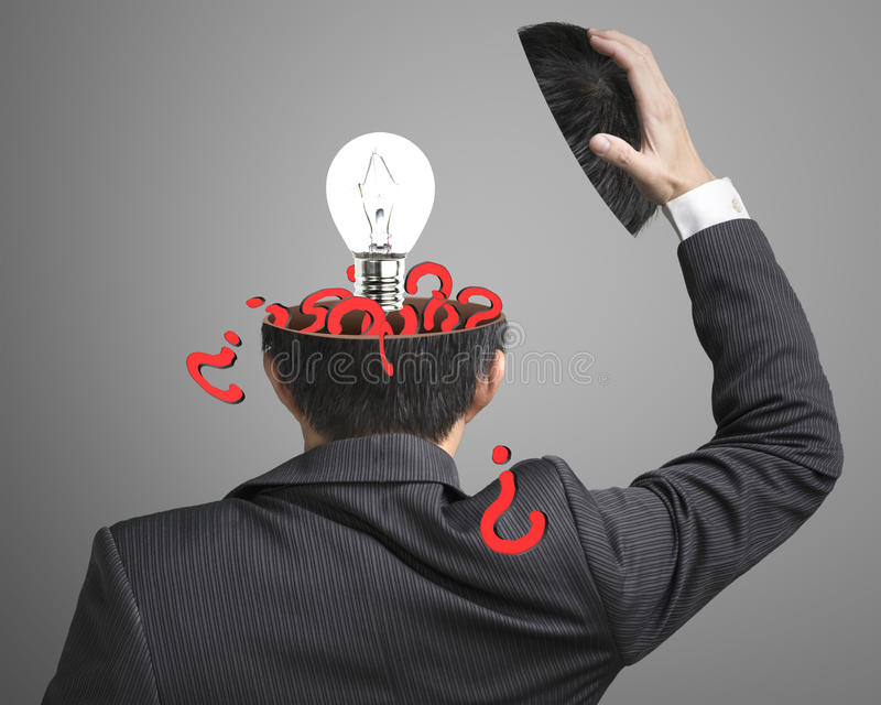 Filled out question inside businessman head with lamp pop out on. Gray background royalty free stock photography