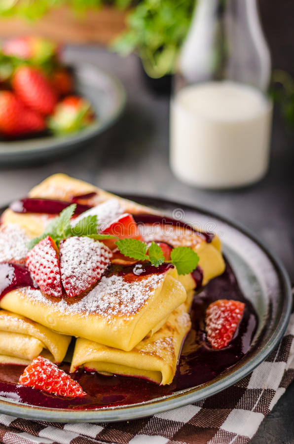 Filled pancakes with strawberries. Fresh berries and sauce stock image