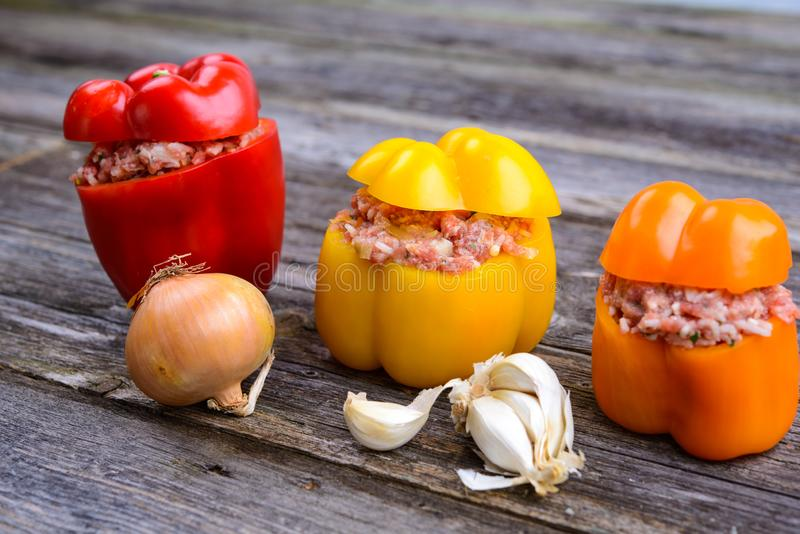 Filled pepper,garlic and onion on wooden ground. Colorful filled pepper,garlic and onion on wooden ground royalty free stock photo