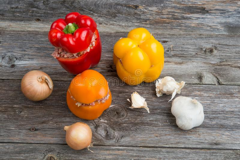 Filled pepper,garlic and onion on wooden ground. Colorful filled pepper,garlic and onion on wooden ground royalty free stock images