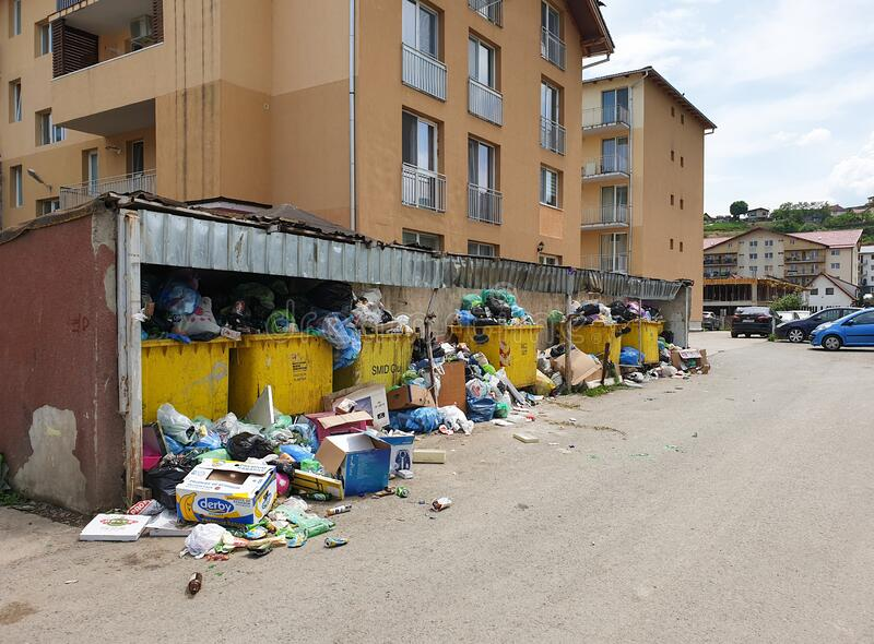 Filled trash bins in populated area in Floresti royalty free stock photography