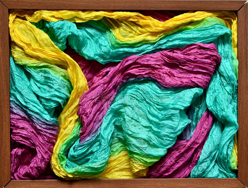 Filled wooden frame. Multicolored silk headscarf filling a wooden frame on a wooden background royalty free stock image