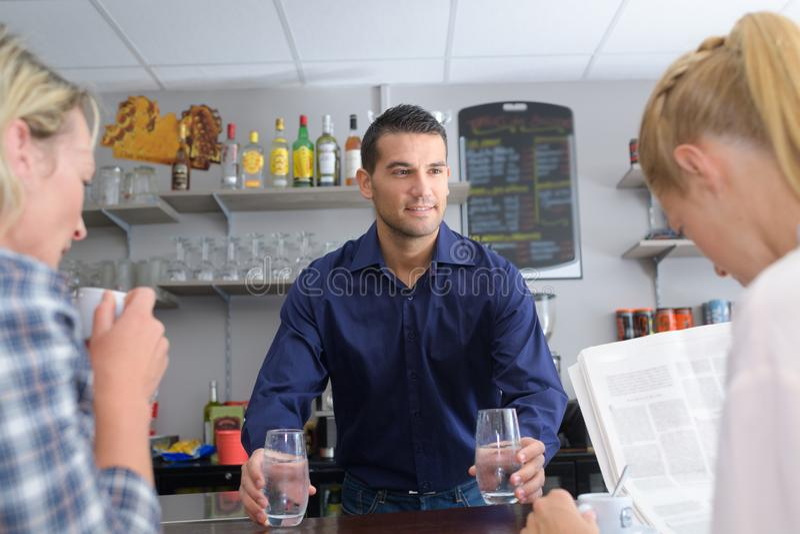 Filles à la barre tandis que barman préparant le cocktail photo libre de droits