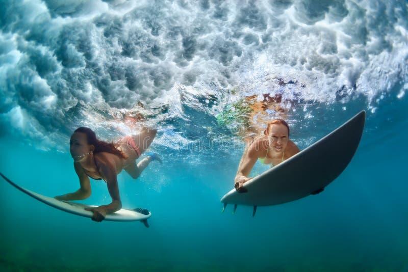 Filles actives dans le bikini dans l'action de piqué sur le panneau de ressac photo stock