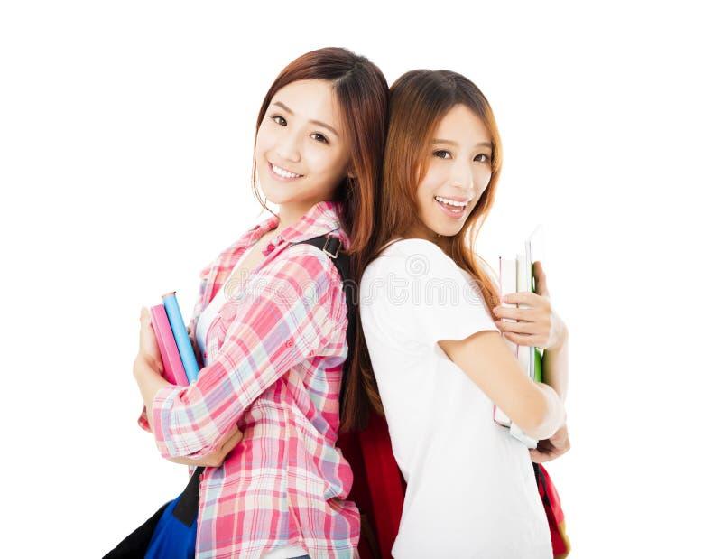 Filles adolescentes heureuses d'étudiants d'isolement sur le blanc photographie stock
