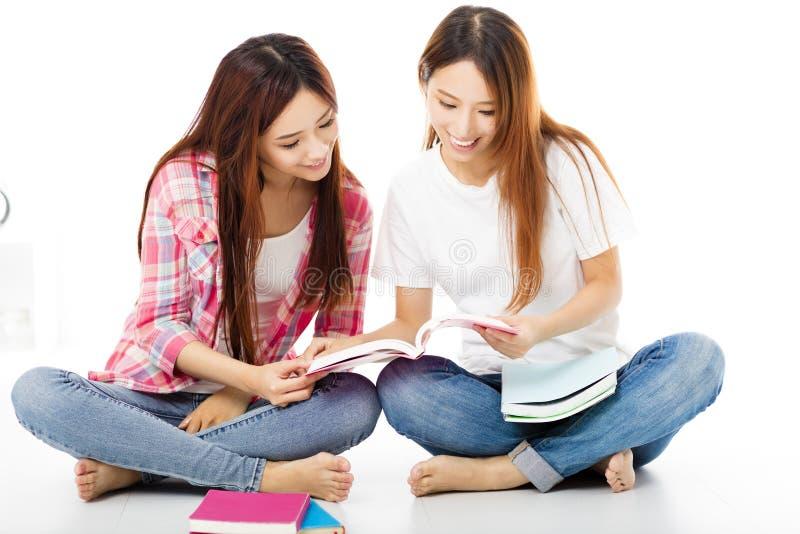 filles adolescentes heureuses d'étudiants observant les livres photographie stock