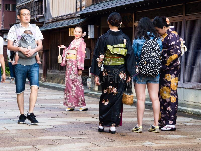 Filles asiatiques dans des kimonos prenant des photos dans le secteur historique de Higashichaya de Kanazawa photographie stock