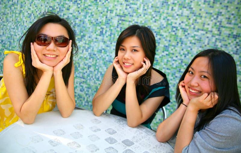 Filles asiatiques de sourire retenant le menton images stock
