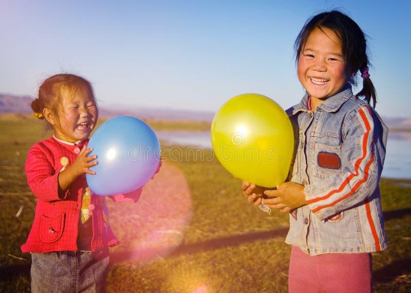 Filles asiatiques jouant le concept mongol rural de ballon de lac image libre de droits