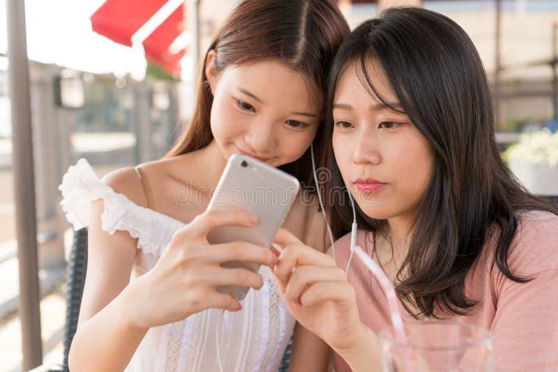Filles asiatiques jouant le téléphone photos libres de droits