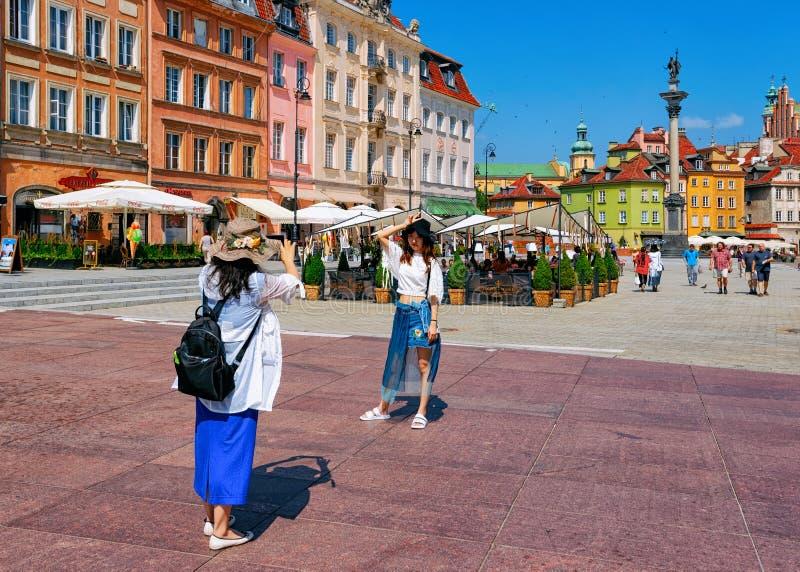 Filles asiatiques prenant des photos à la colonne de Sigismund sur la place de château dans la vieille ville de Varsovie en Pol image stock