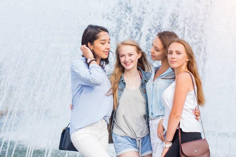 Filles assez gaies de jeunes parlant près de la fontaine dans la ville photographie stock