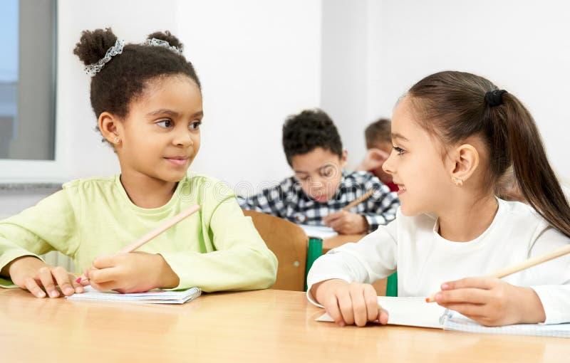 Filles au bureau dans la salle de classe, regardant l'un l'autre, posant photographie stock libre de droits