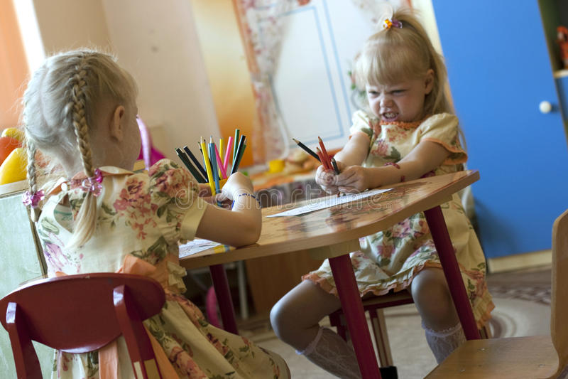 Filles avec des crayons dans le jardin d'enfants photographie stock libre de droits