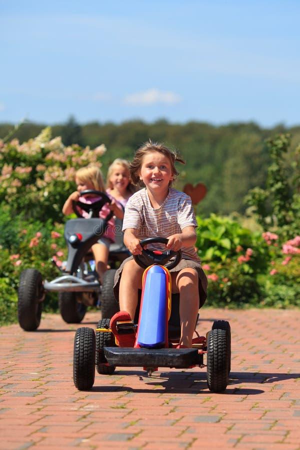 Filles avec le sourire extérieur de véhicules de jouet photo libre de droits