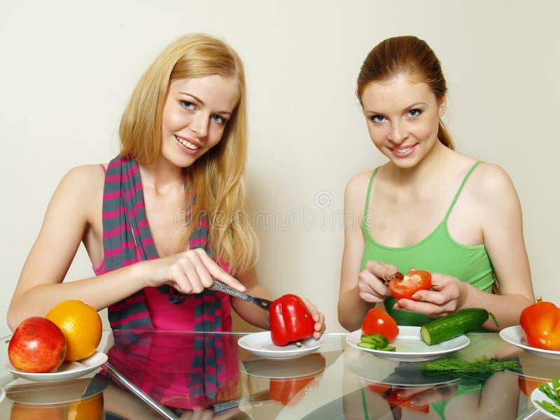 Filles avec les légumes et le fruit derrière une table image libre de droits