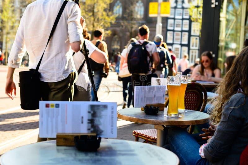 Filles buvant de la bière de lumière froide en café de rue à Amsterdam photos libres de droits