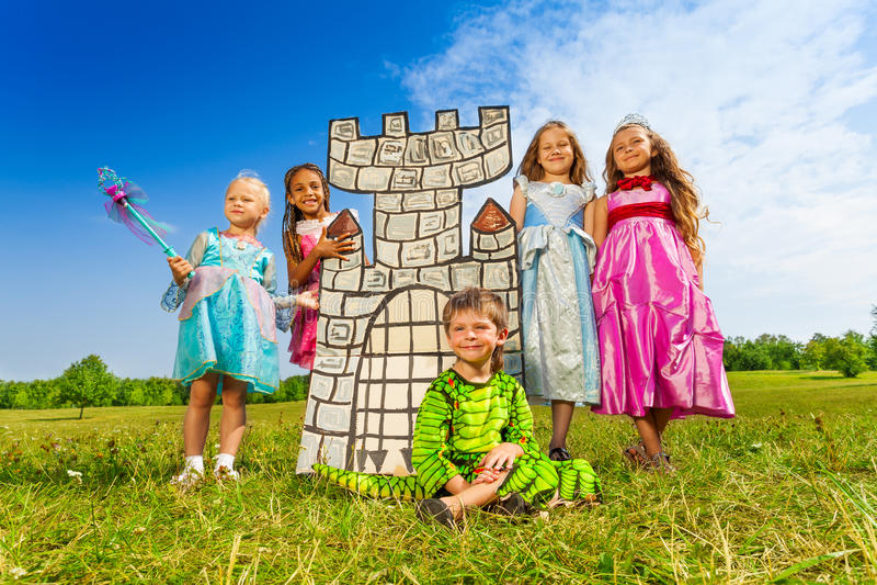 Filles comme princesses et garçon dans le costume de monstre photo libre de droits