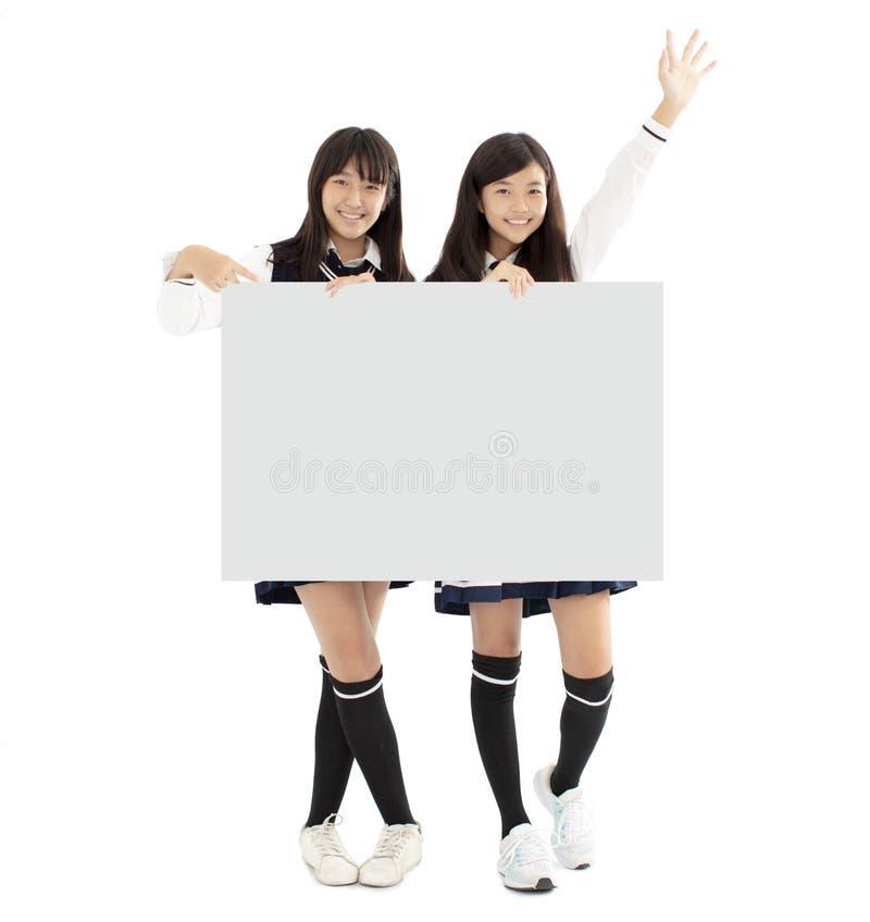 Filles d'étudiant d'adolescent avec le conseil blanc vide images stock